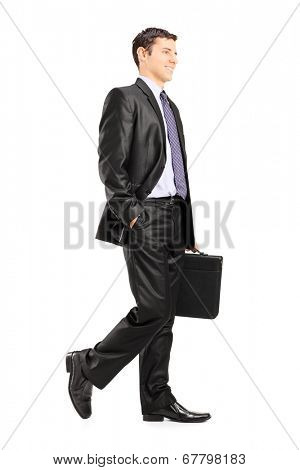 Happy business man holding a briefcase and walking isolated on white background
