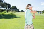 stock photo of ladies golf  - Lady golfer teeing off for the day on a sunny day at the golf course - JPG