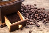 stock photo of coffee grounds  - Vintage coffee bean grinder and fresh ground coffee on wooden top next coffee beans - JPG