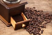 picture of coffee grounds  - Vintage coffee bean grinder and fresh ground coffee on wooden top next coffee beans - JPG