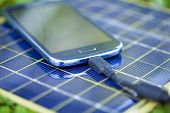 stock photo of solar battery  - Solar Mobile Phone Chargers on grass in nature - JPG