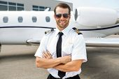 stock photo of jet  - Portrait of confident pilot smiling in front of private jet - JPG