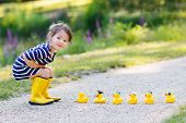 stock photo of ducks  - Adorable little girl of 2 playing with yellow rubber ducks in summer park - JPG