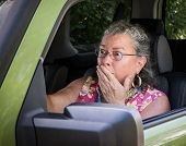 foto of blood drive  - Sweaty hot senior woman driver looking terrified holding hand to mouth in driver - JPG