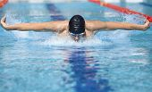 stock photo of breathing exercise  - professional swimmer in cap breathing performing the butterfly stroke in swimming pool - JPG