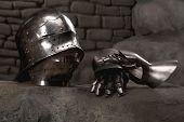 stock photo of armor suit  - Closeup of knight armor helmet and gloves on the dark stone wall background - JPG
