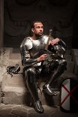 image of arsenal  - Portrait of medieval knight in armor with shield and sword sitting on steps of ancient temple with skull - JPG