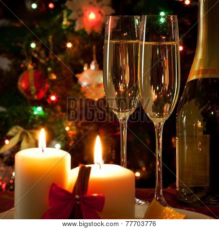 Champagne glasses with New Year decoration on fir background