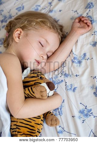 cute little girl asleep hugging toy