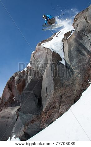 Skier jumping  from high cliff.