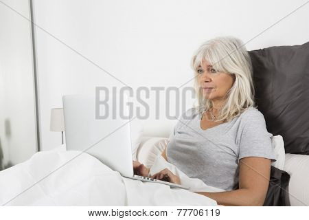Sitting Mid Age woman with a laptop in bed
