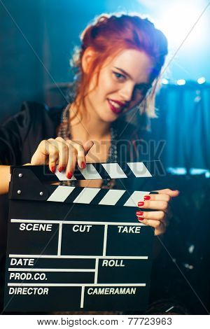 Young woman film director with clapper portrait. Blue light on background. Focus on clapper.