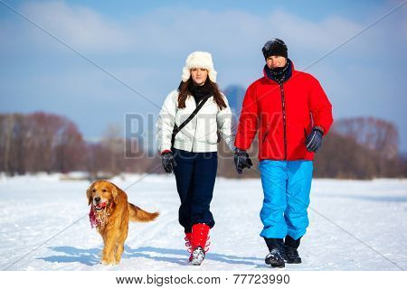 Young couple walking with dog. Cold winter season and snowfield.