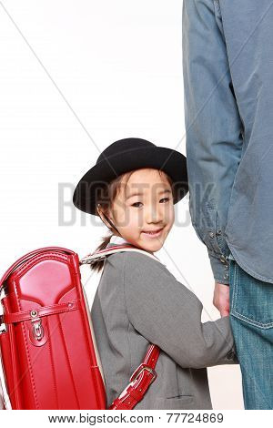 Japanese school girl with satchel walking to school with her father