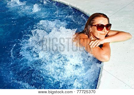 Beautiful girl relaxing in jacuzzi. Spa background