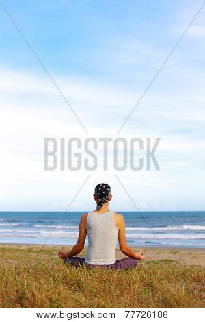 man sitting by the ocean and meditating