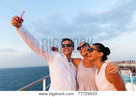 group of friends taking self portrait using smart phone on cruise