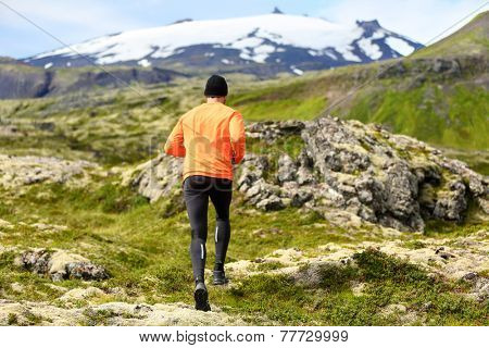 Sport athlete - exercising trail runner running. Active male fitness model training and jogging outdoors in beautiful mountain nature landscape by Snaefellsjokull, Snaefellsnes, Iceland.