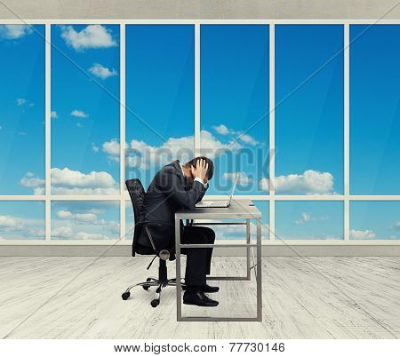 depressed businessman sitting at the table with laptop and covering his head in the light office with big windows
