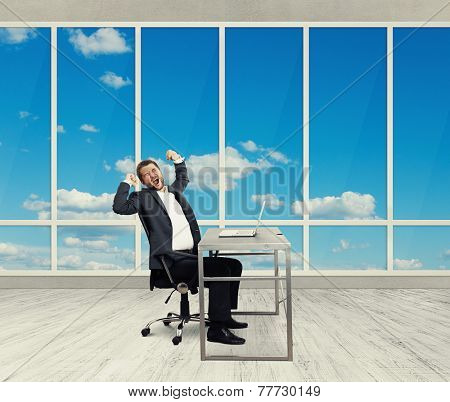 fatigued businessman yawning and stretching oneself in the light office with big windows