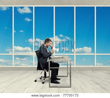 angry businessman screaming with megaphone and looking at laptop in the light office with big windows