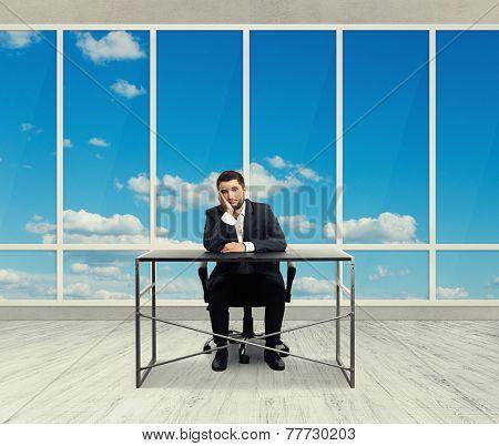 sad man sitting in the empty office