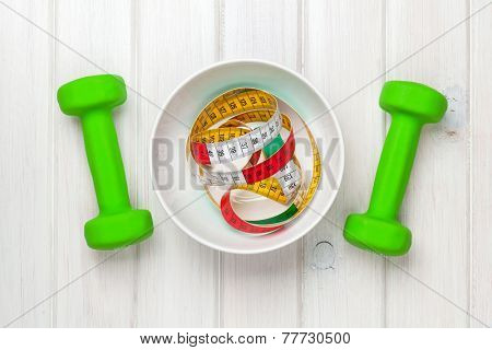 Dumbells and tape measure in bowl over wooden background. Fitness and health. View from above