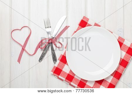 Empty plate, silverware and valentines day heart shaped ribbon. View from above over white wooden table