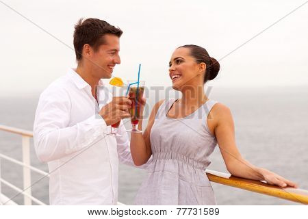 happy newlywed couple on honeymoon drinking cocktails on a cruise ship