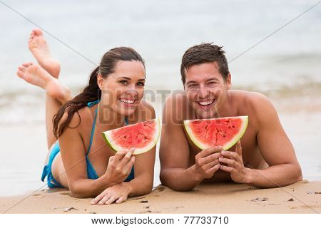 happy young couple eating watermelon on beach