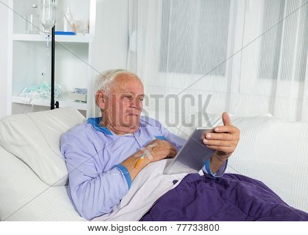 Older man receives infusion and uses a digital tablet