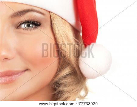 Cute Santa girl, half face of beautiful woman wearing red festive hat isolated on white background, happy Christmas holiday concept