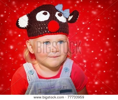 Closeup portrait of a little baby girl wearing funny Rudolph hat over red snowy background, Christmas celebration concept