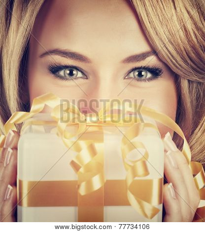 Closeup portrait of sexy woman with beautiful eyes holding in hands Christmas gift, receive romantic present, perfect festive makeup, luxury New Year celebration