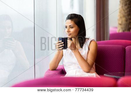 peaceful woman having cup of coffee in coffee shop