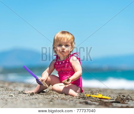 cute baby girl playing in the sand with a shovel on the beach