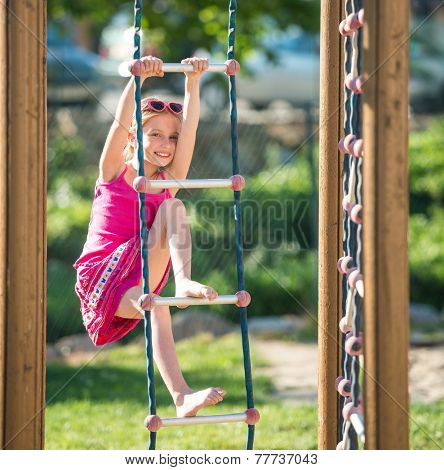 Pretty smiling  little girl on outdoor playground equipment