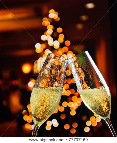 Champagne Flutes With Golden Bubbles On Christmas Lights Decoration Background