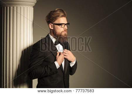 Attractive business man fixing his suit with both hands while looking away from the camera.