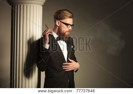 Blonde business man looking down while holding a cigarette in his right hand. He is fixing his suit with his left hand.