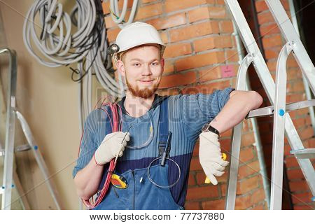 electrician builder engineer worker with cable wiring at indoor construction site
