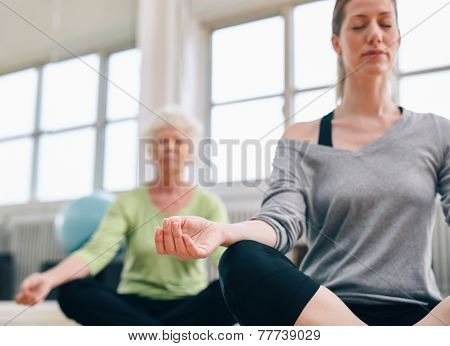 Relaxed Fitness Women Practicing Yoga At Gym