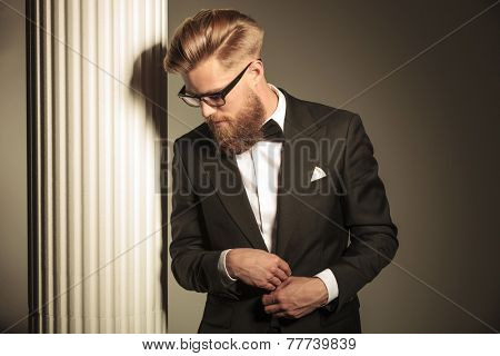 Elegant business man wearing a tuxedo posing near white column, looking down while closing his jackt.