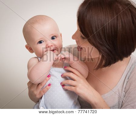 Young Mother Holding Smiling Baby Boy In Arms