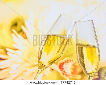 Champagne Flutes With Golden Bubbles On Wedding Flowers Background