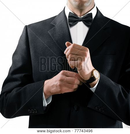 hands of the man who in a black tuxedo puts on his watch
