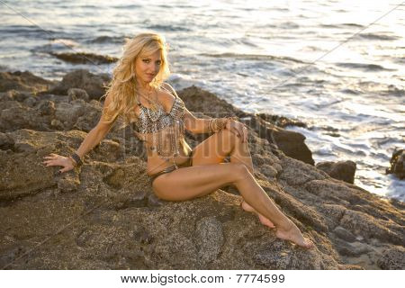 Flashy Blonde Woman On Rocks At The Ocean With Copy Space