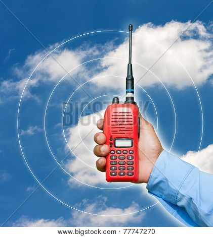 Red Portable Radio Transceiver In Hand On Blue Sky