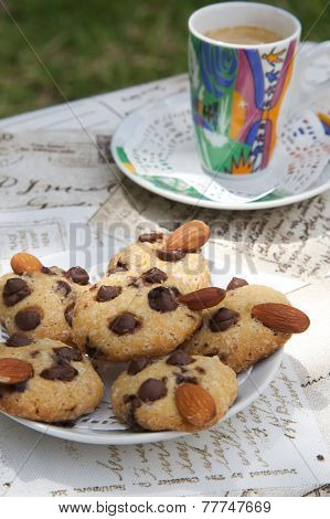 Shortcakes with chocolate chips and nuts on the white plate. A cup of coffee in the background