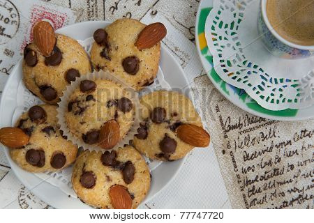 A plate of mini shortcakes with chocolate chipsalmond nuts and a cup of espresso. Top view